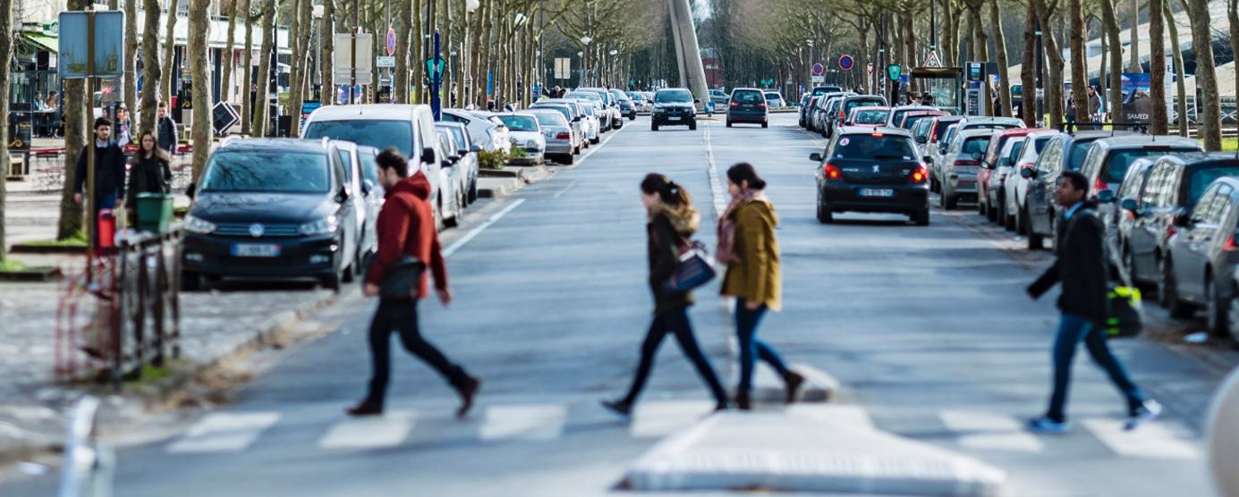 Des passants travers un passage piéton de l'avenue Ampère à la Cité Descartes