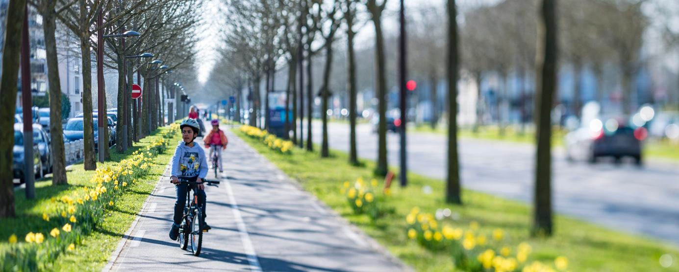 Des personnes sur des vélos sillonnent une piste cyclable du centre ville de Bussy Saint-Georges