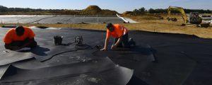 Deux ouvriers installent une géomenbrane bassins lors du chantier de Villages Nature Paris