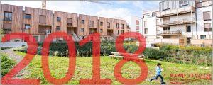 """Au premier plan, """"2018"""" est écrit en rouge. Au second plan, figure des logements de l'écoquartier de Montévrain"""
