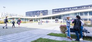 Quelques étudiants se promènent dans la cours, devant l'immeuble le Bienvenüe (campus de la Cité Descartes)