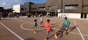 Collégiens jouant au football dans la cour de l'école Louis de Vion dans l'écoquartier de Montévrain (Bâtiment ENR PASSIF)