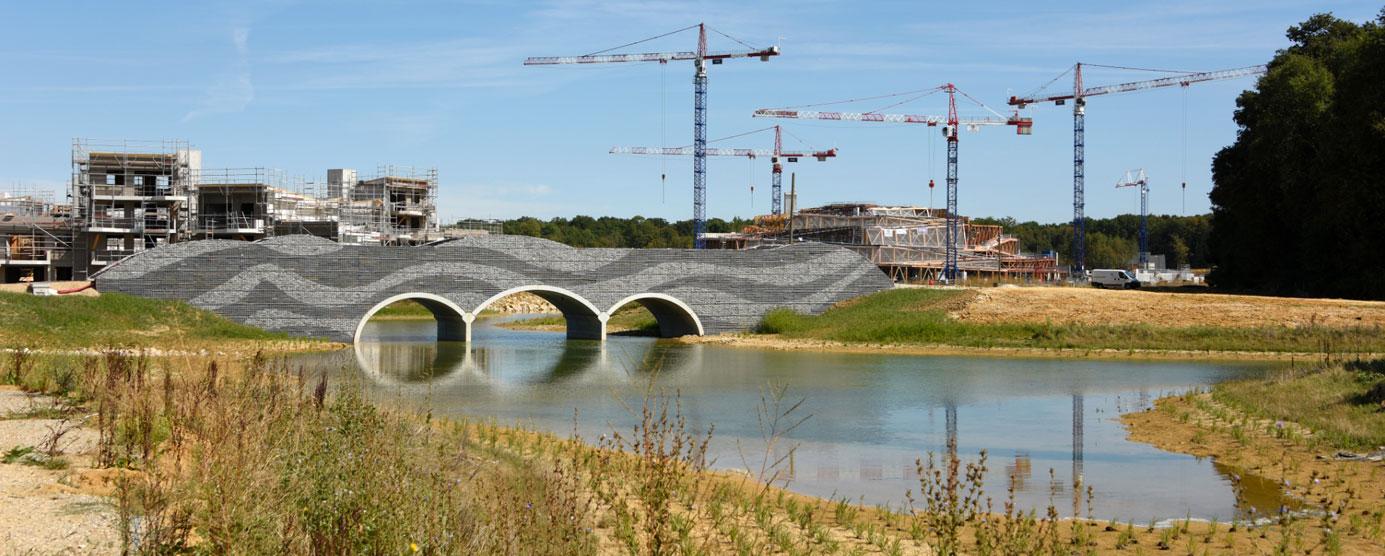 Au premier plan : une rivière est surplombée par un pont. Au second plan : plusieurs grues du chantier de Villages Nature Paris