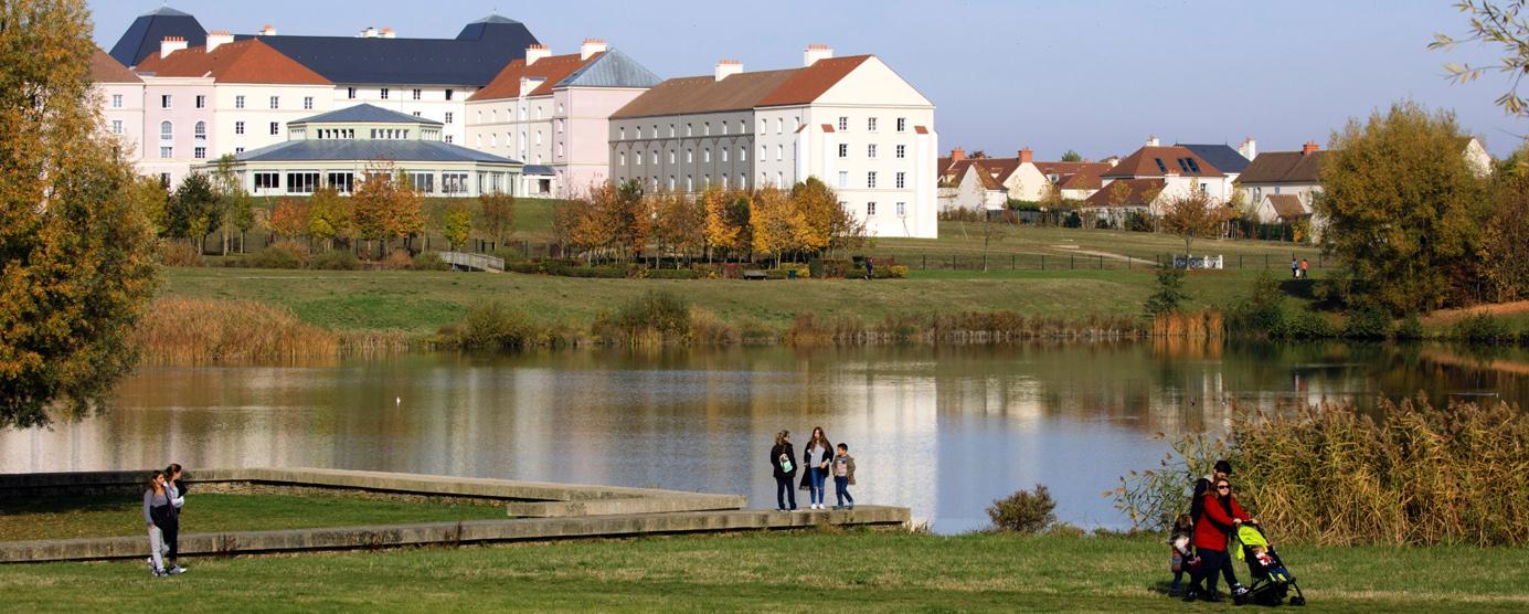 Au premier plan : lac et promeneurs. Au second plan : résidence touristique : hôtels B&B à Magny-le-Hongre