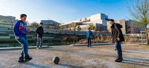 Photographie de quatre adolescents jouant au football aux abords du collège et lycée international de l'est parisien à Noisy-Bry