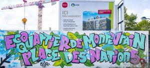 """Fresque de lettrage sur une palissade de chantier du programme de logements coeur du Montévrain. On peut y lire """"Écoquartier de Montévrain - Place des Nations"""""""