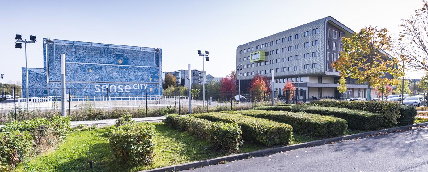 Photographie prise au sol, aux abords de l'Ecole des Ponts ParisTech, bâtiment Corolis (ENR+) et de l'Equipex Sense-City, sur le campus de la Cité Descartes